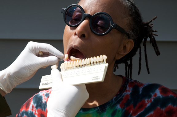 Dental technician Alison Tuton assessing the colour contrast of the author's teeth before crafting a custom dental implant. Photo by Joanne Bealy