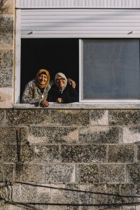 Two women enjoy the comfortable December weather in the window of a home. At-Tur, East Jerusalem.