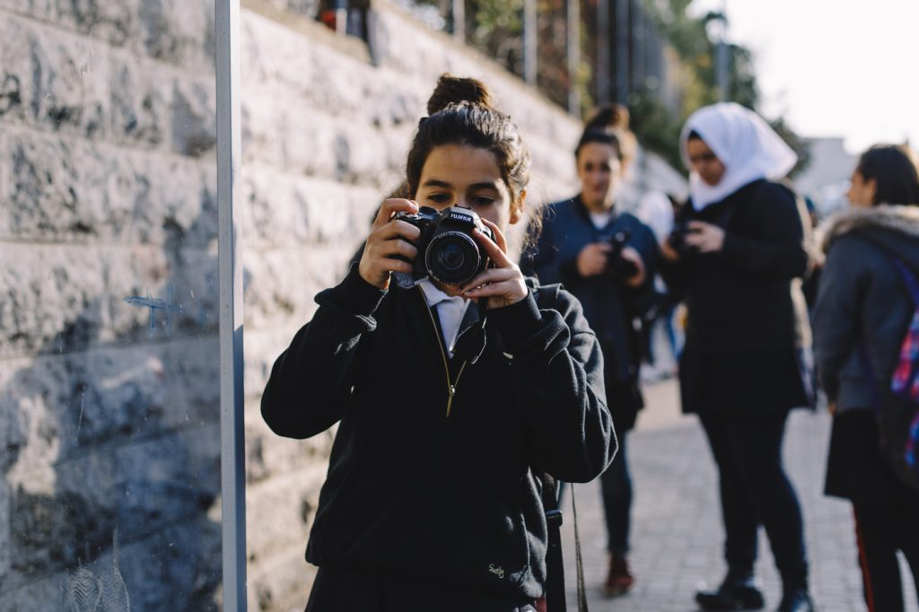 A girl, part of a group of students taking photos for a class as I walked down their school's street. At-Tur, East Jerusalem.