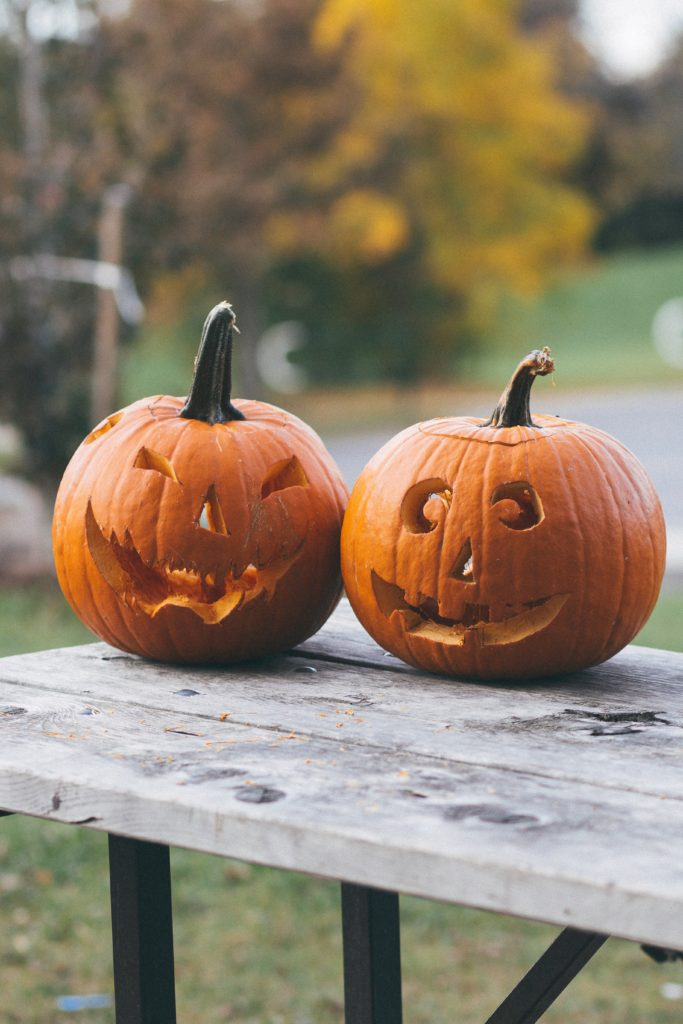 Two unlit jack-o-lanterns on a wooden table.