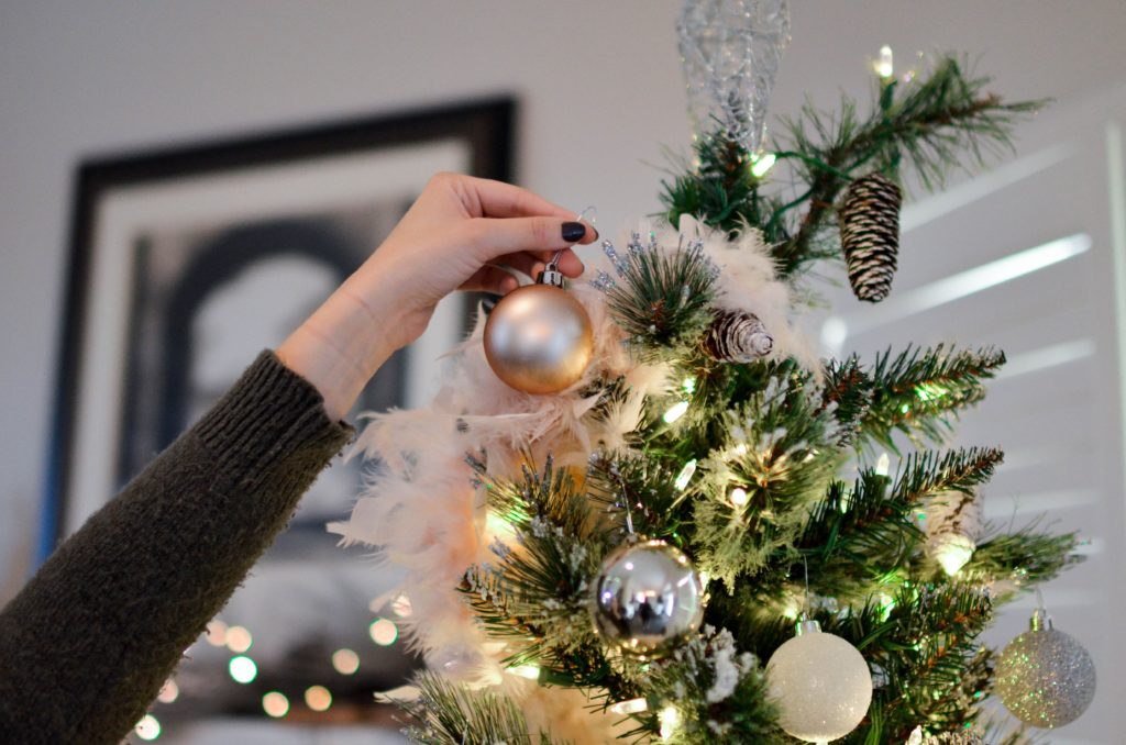 In this image: someone putting an ornament on a Christmas tree.