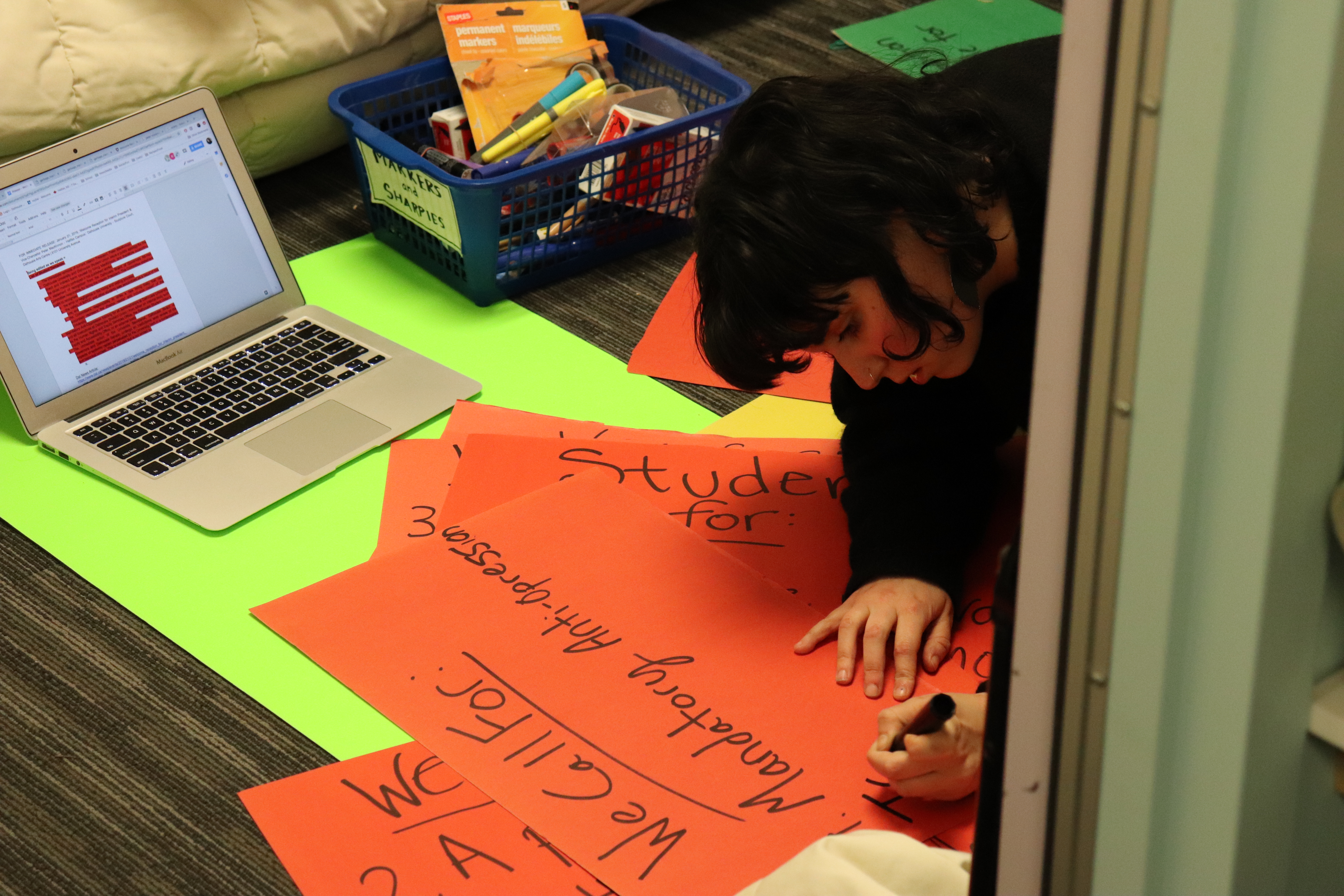 University of Kings College student, Pheobe Lamb, makes signs at the NSPPIRG office before the protest.