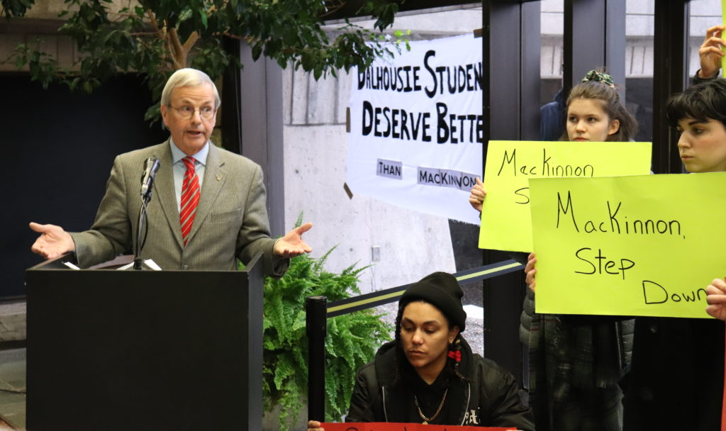 In this image: MacKinnon speaks while the student protesters silently hold their signs.