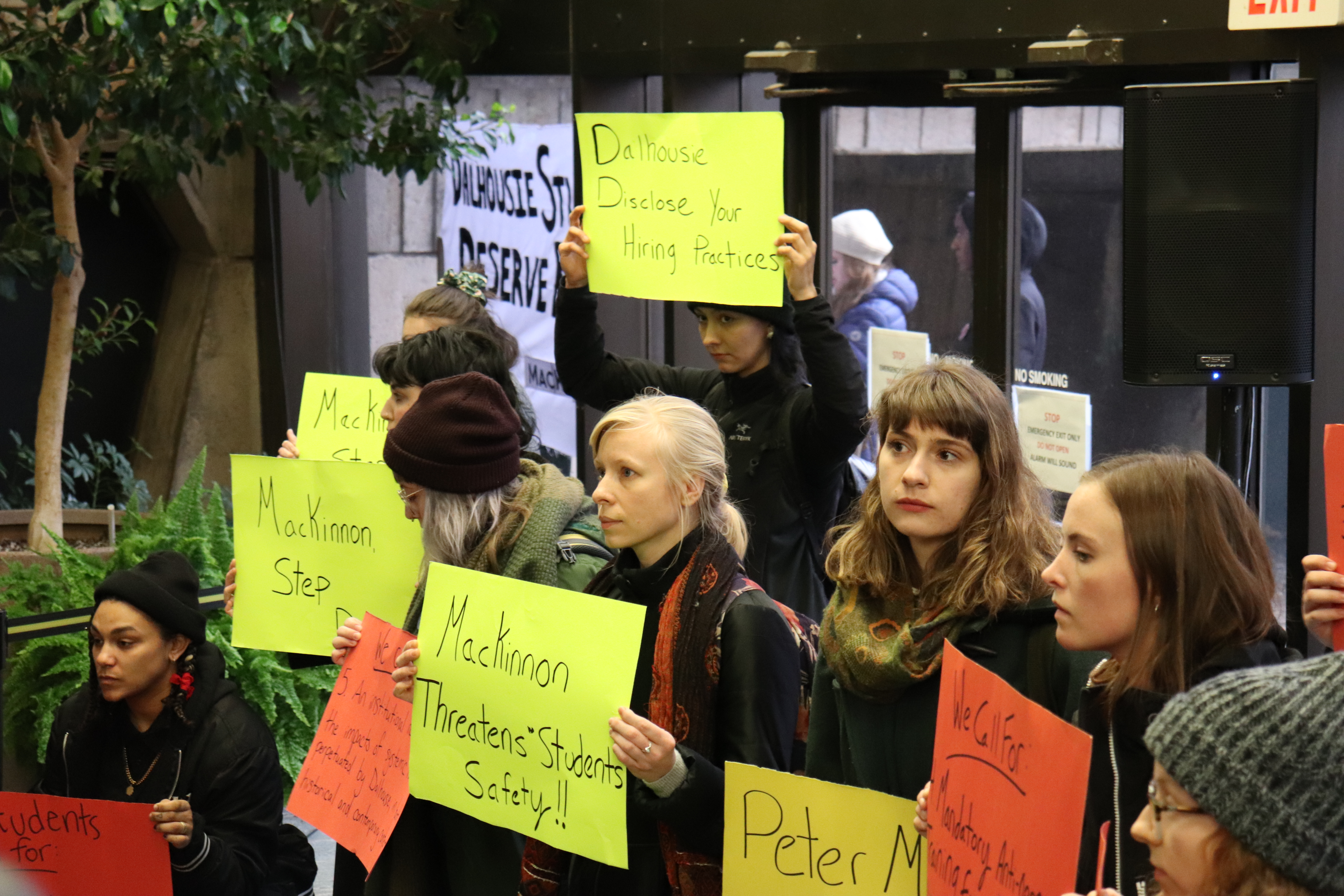 In this image: Dalhousie students stand in the Arts Centre holding signs protesting Peter MacKinnon.
