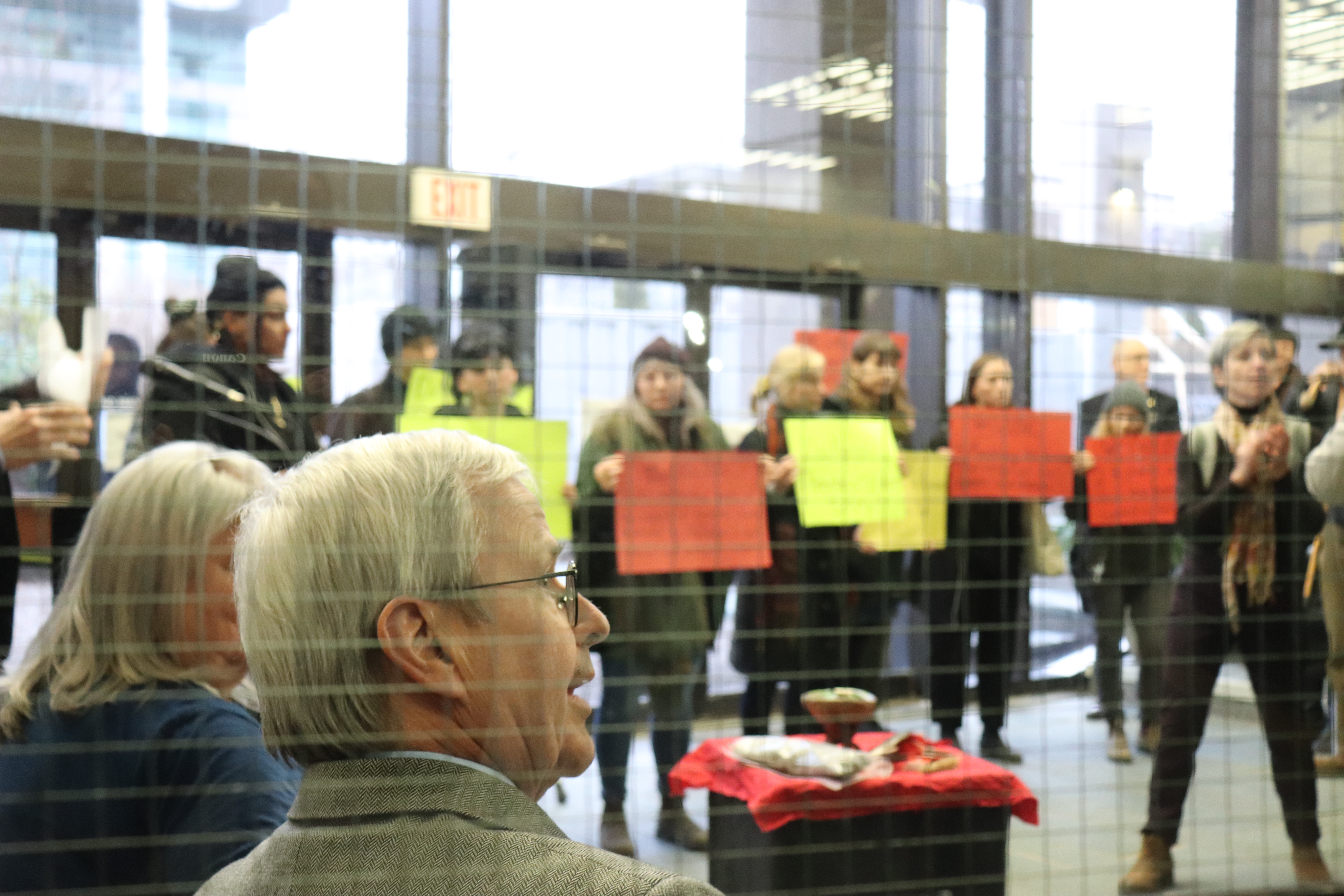 In this image: MacKinnon sits down after his speech, students hold signs in front of him.