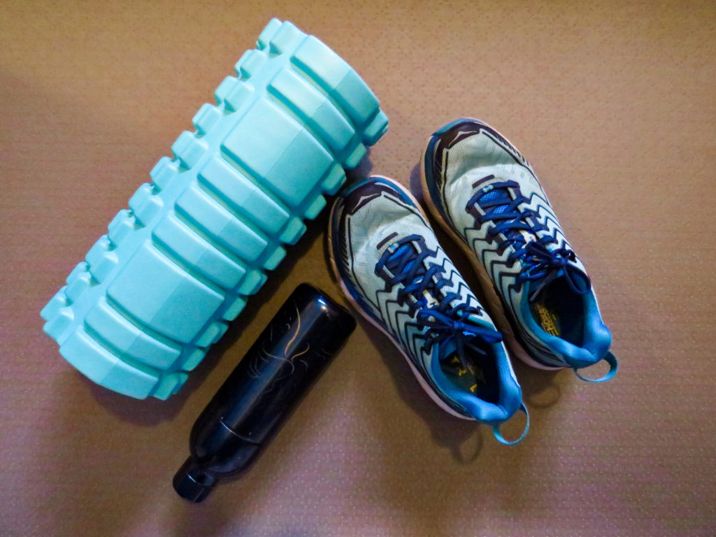 In this image: A foam roller, a water bottle and a pair of running shoes.