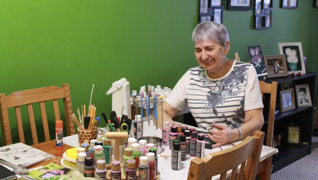 In this image: Dorothea McCorriston in front of her paint supplies.