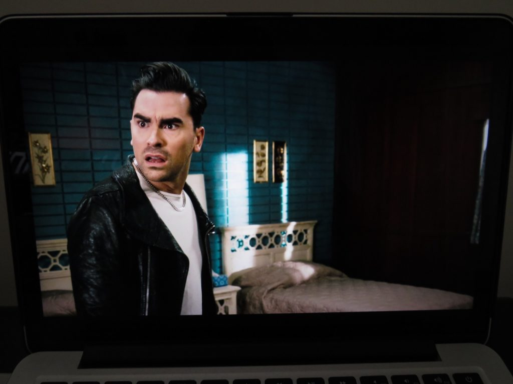 In this image: Dan Levy on-screen in a still shot of Schitt's Creek playing on a laptop.