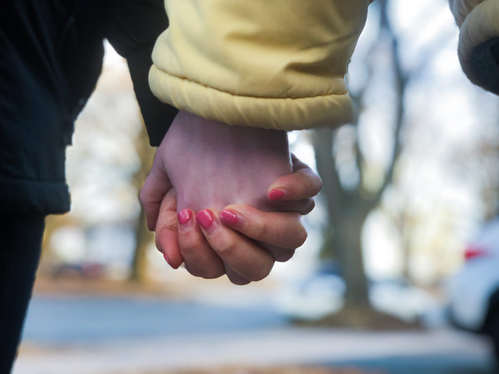 In this image: Close-up of holding hands.