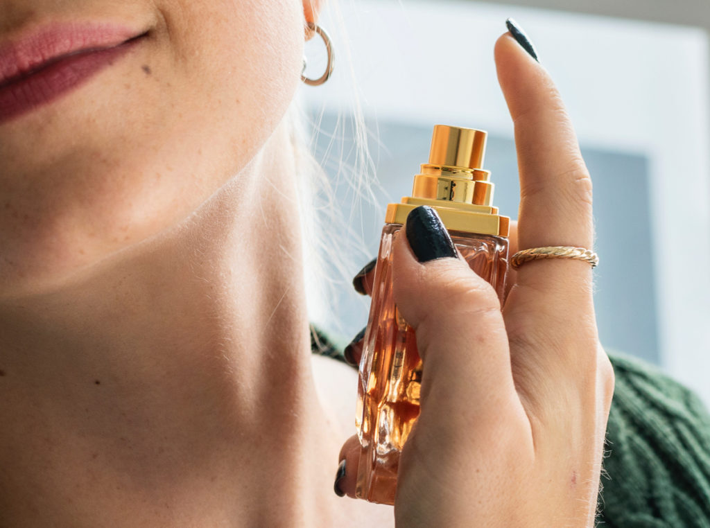 In this image: a person about to spray perfume on their neck.