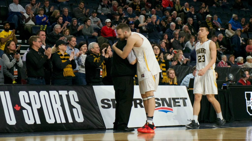 In this image: Mike Shoveller hugs Rick Plato while he and Kevin Duong walk off the court for the final time of their university careers.