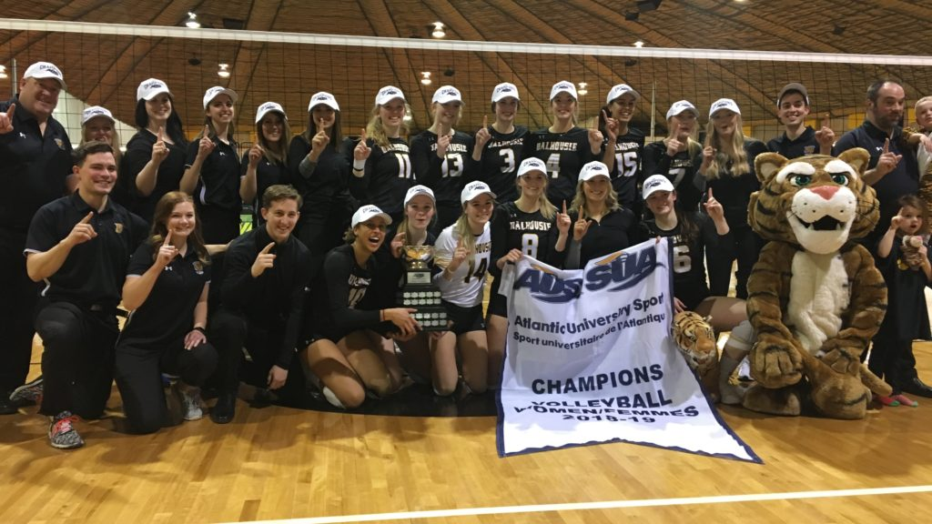 In this image: he Dalhousie women's volleyball team pose for a championship photo in front of the volleyball net at Dalplex on March 2.