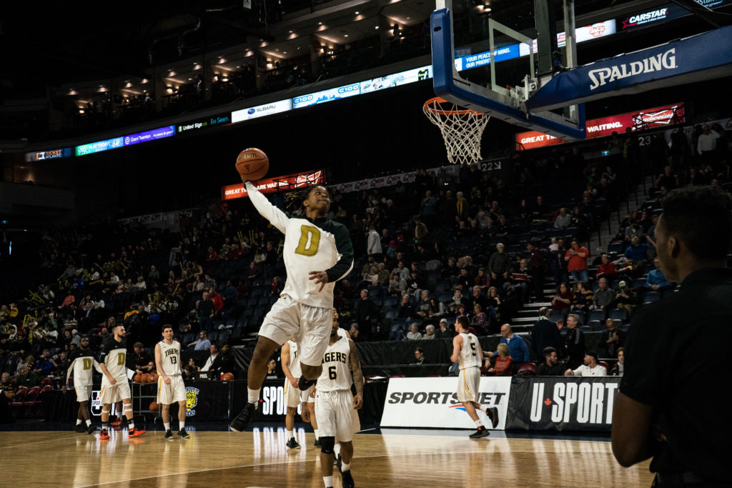 In this image: A Dalhousie player goes to dunk the basketball.