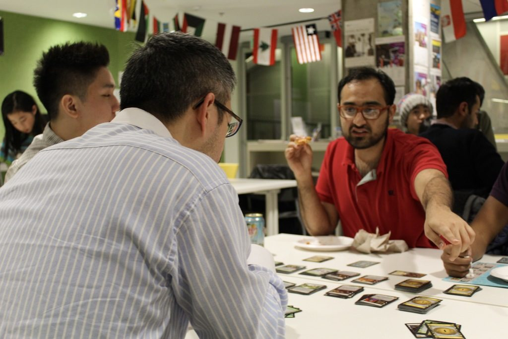 In this image: A man points to something while playing a card game.