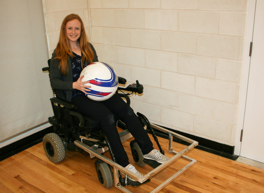 In this Image: Madison Campbell sits in a power wheelchair holding a powerchair soccer ball.