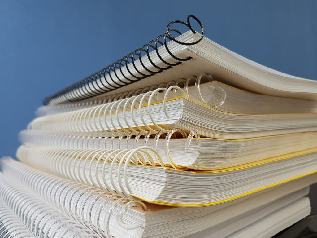 In this image: a stack of wire-bound notebooks.