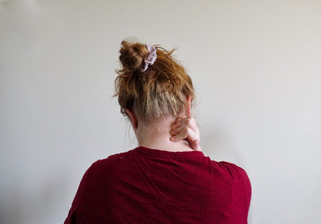 In this image: back of woman rubbing her neck
