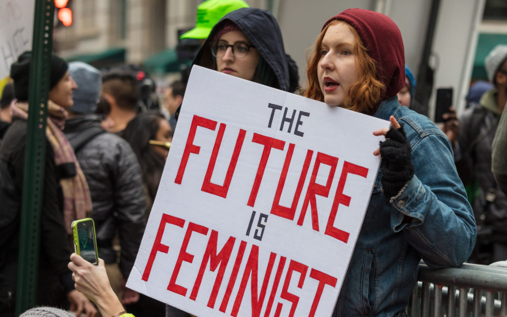"In this image: A woman holds a sign at a rally that says ""the future is feminist."""