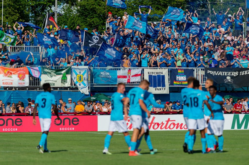 In this image: The crowd cheers for the Halifax Wanderers team at a game.