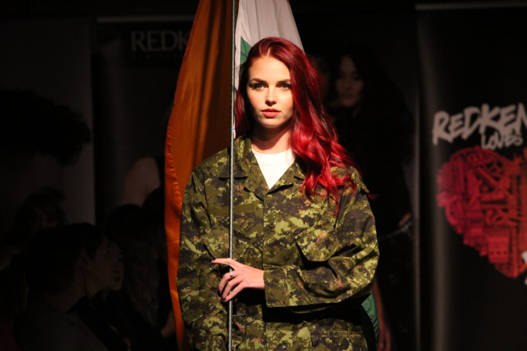 In this image: A model wears a camoflauge outfit.