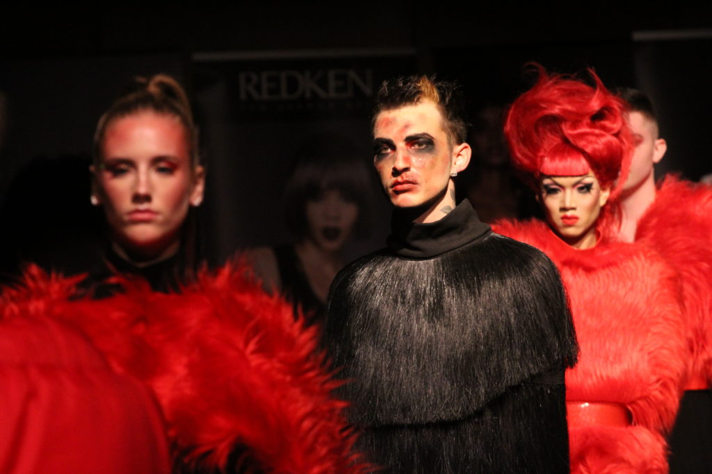 In this image: Three models model the runway in black and red.