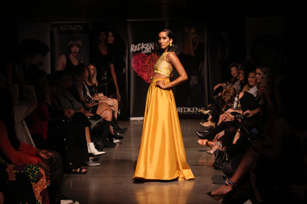 In this image: A model poses on the runway in a yellow gown.