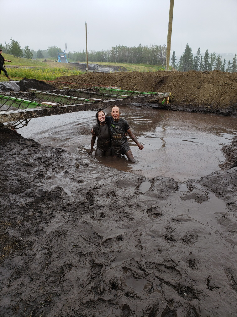In this image: Art Noble and his granddaughter covered in mud in a hole.