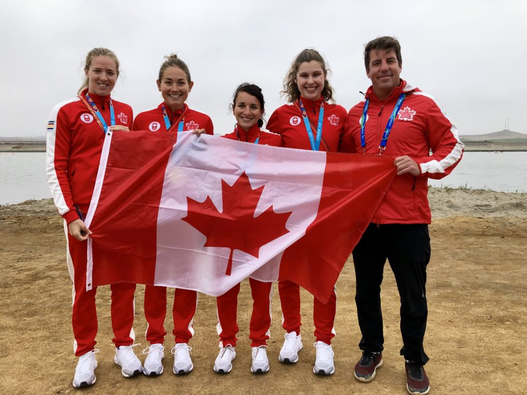 In this image: Five athletes from Team Canada pose with the Canada flag.