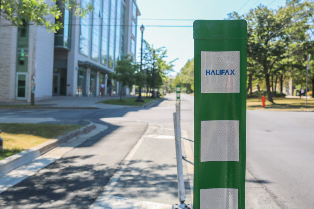 In this image: A close-up of one of the new green barriers on bike lanes.