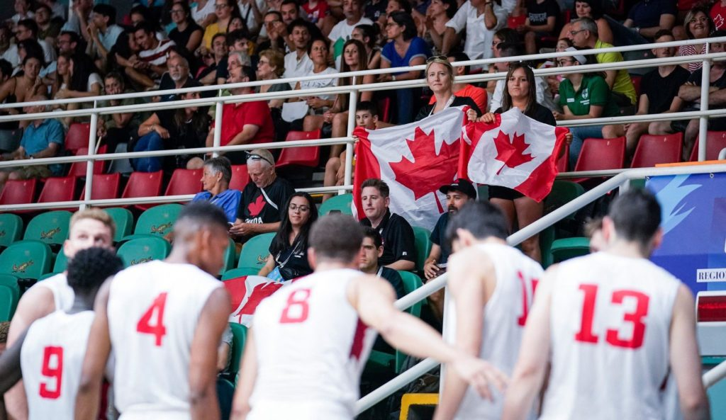 In this image: Two members from the crowd hold Canada flags.