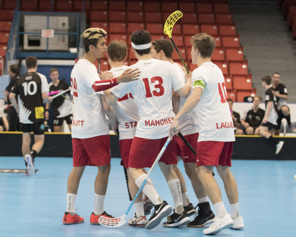 In this image: Team Canada from Men's World Floorball Championships huddles together.