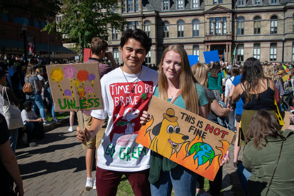 In this image: Two students pose with their signs.