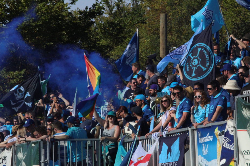 In this image: Fans watch from the sidelines with blue-coloured gear.