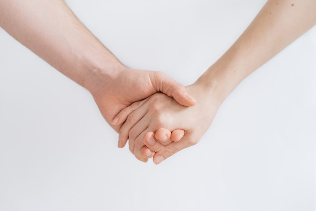 In this image: Two hands holding.