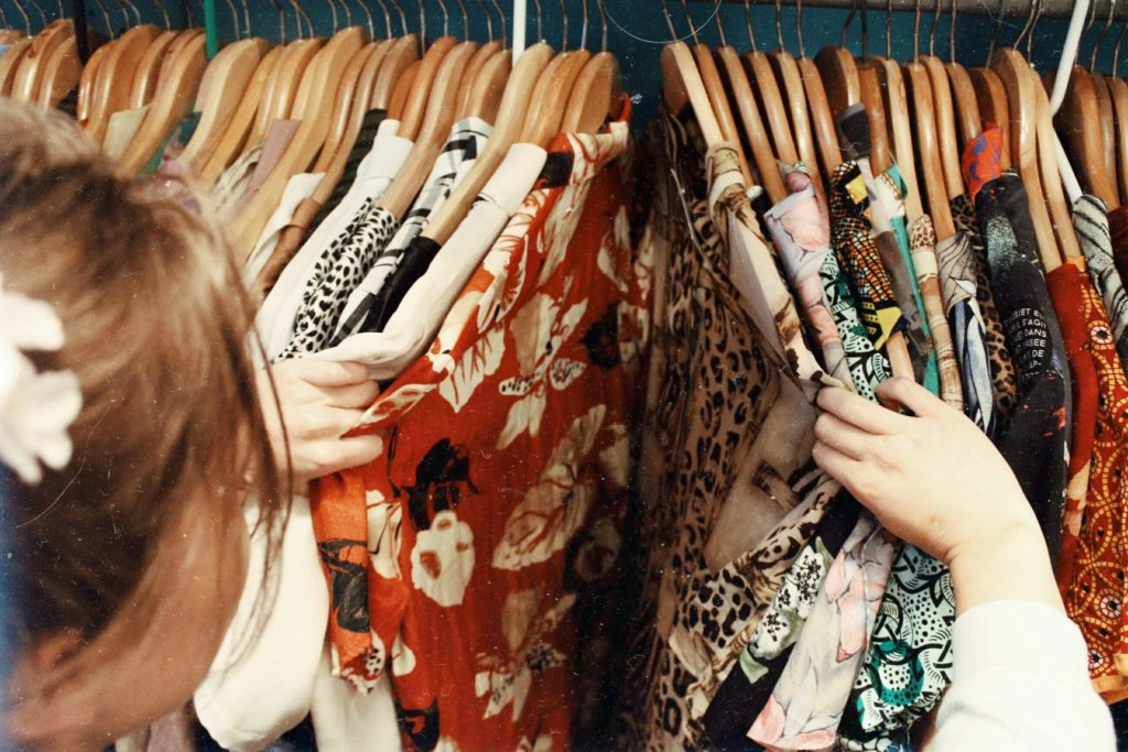 In this image: someone browsing through clothes on a hanging rack.