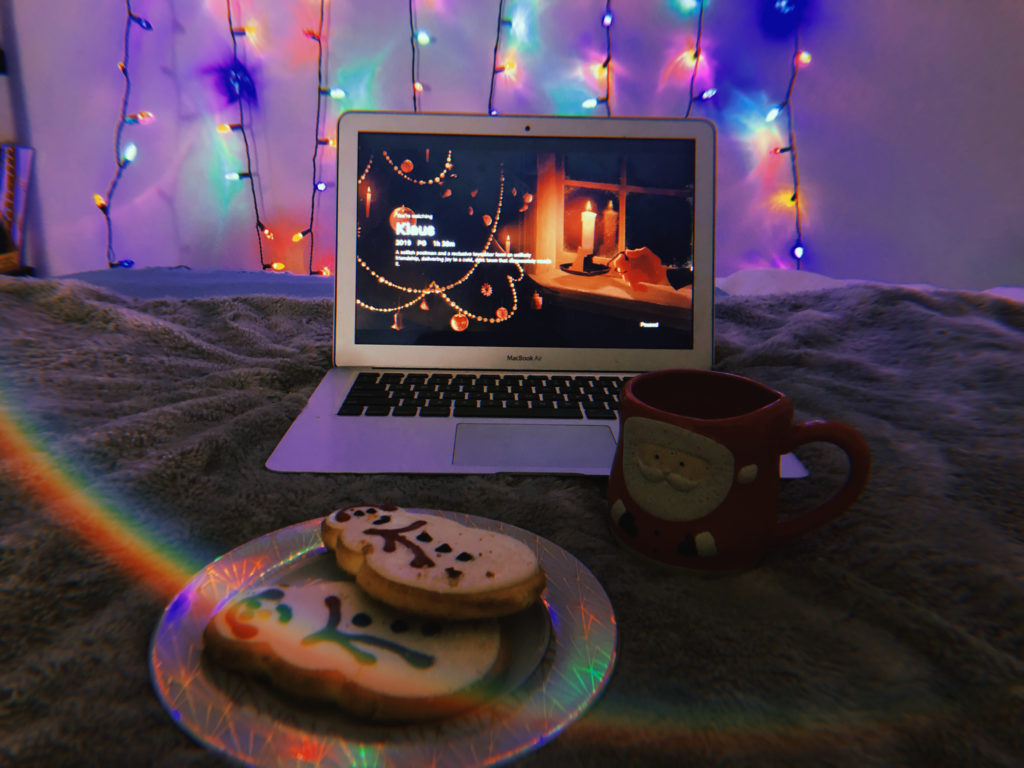 In this image: A MacBook Air with Klaus playing and cookies in the foreground.