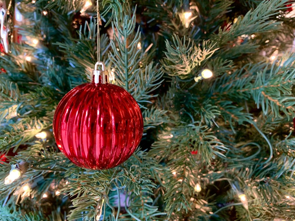 In this image: A red ornament on a Christmas tree.