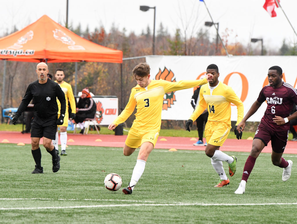 In this image: A Dalhousie Tiger goes to kick the ball during a game against the Saint Mary's Huskies.