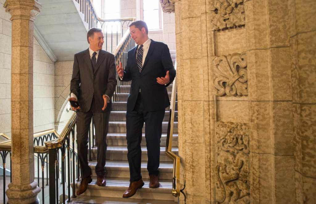In this image: Maxime Bernier and Andrew Scheer walk down a staircase at Parliament Hill.