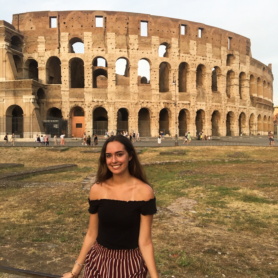 In this image: Olivia Ward poses in front of the Colesseum in Rome.