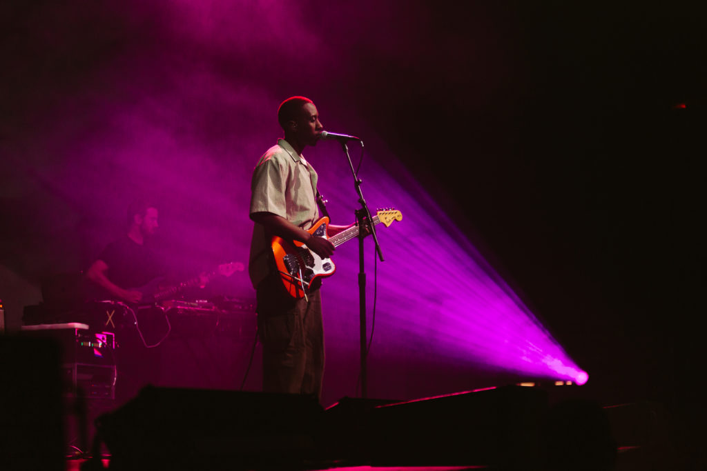 In this image: Daniel Caesar on stage playing guitar.