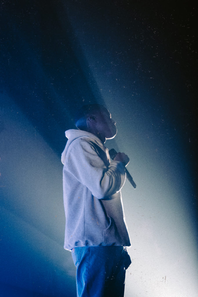 In this image: Close up of Daniel Caesar on stage.