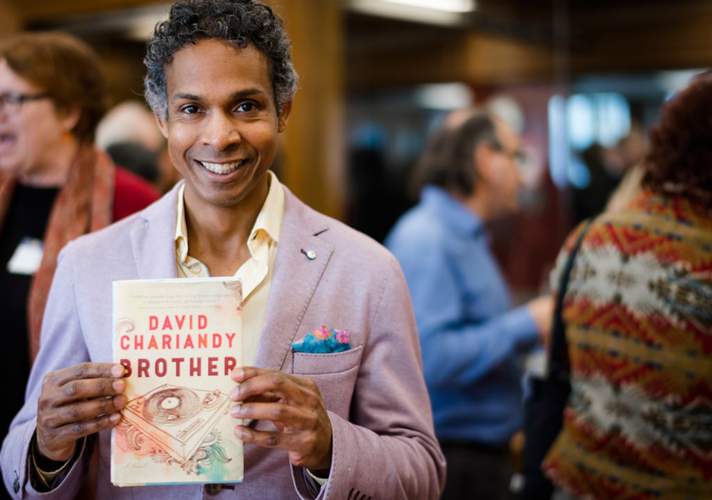 In this image: David Chariandy holding his book Brother.