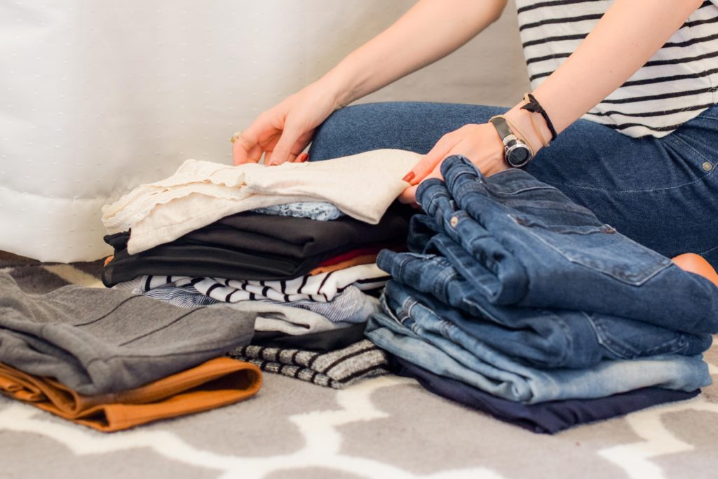 In this image: A person folds a pile of clothes.