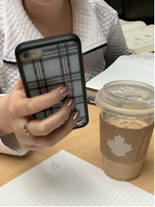 In this image: A person holds a cellphone beside a Tim Horton's drink.