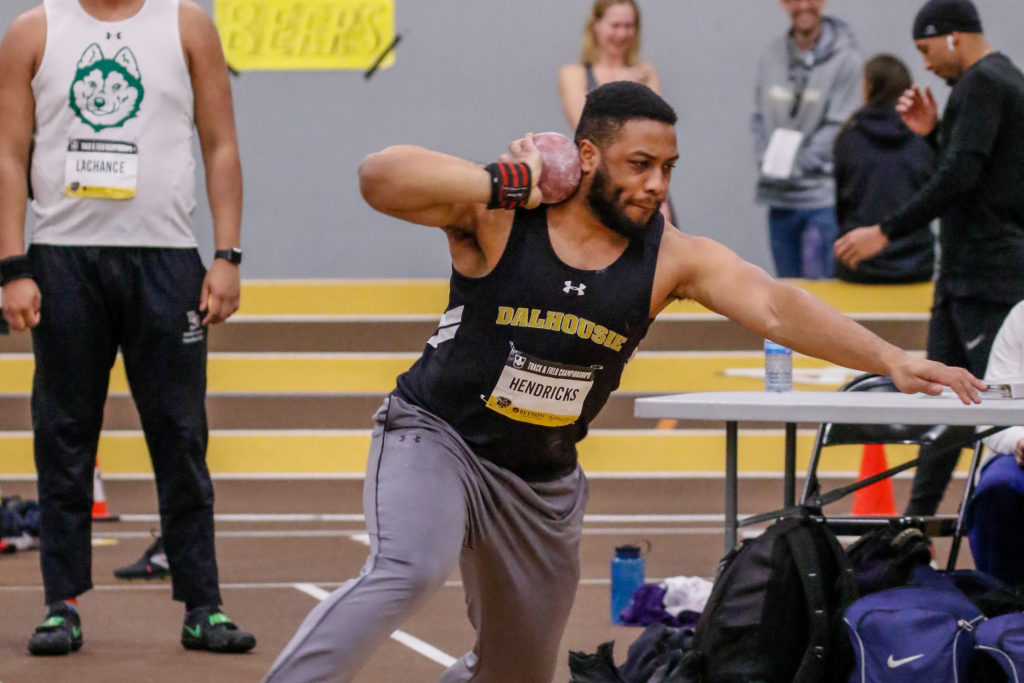 In this image: Andre Hendricks preparing to throw a shot put.