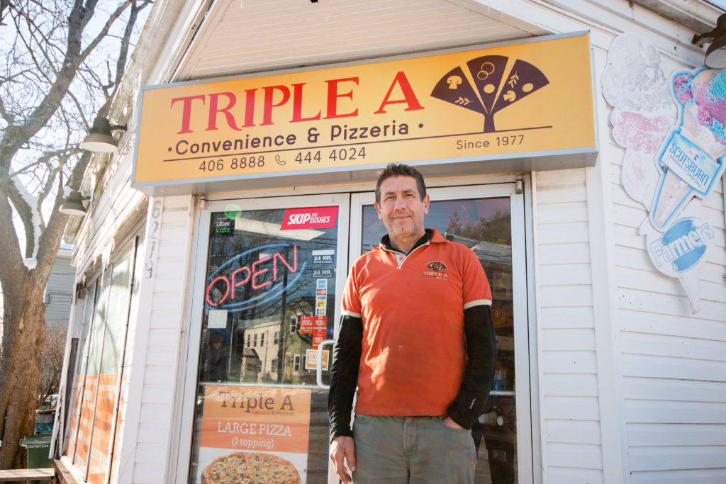 In this image: John Amyoony stands in front of Triple A.