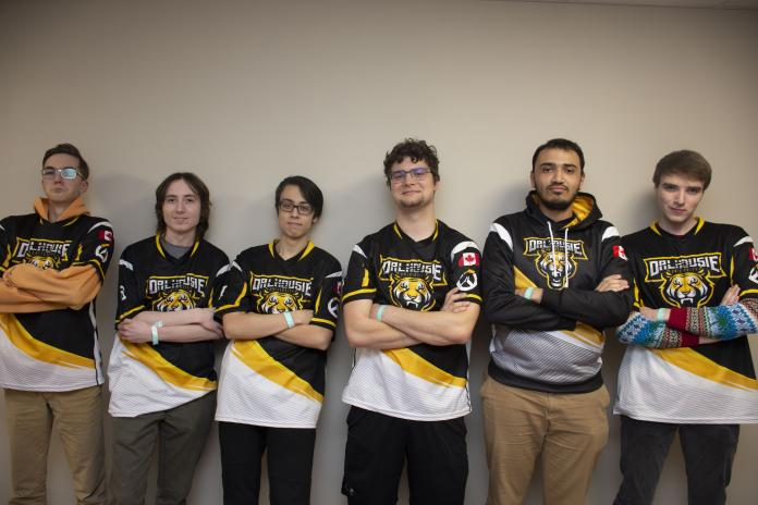 In this image: Dalhousie University's Overwatch team lines up against a white wall.