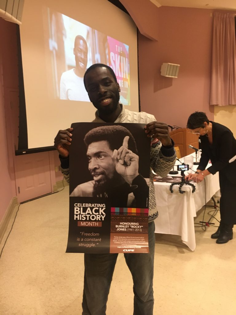 In this image: Desmond Cole holds a Black History Month poster.
