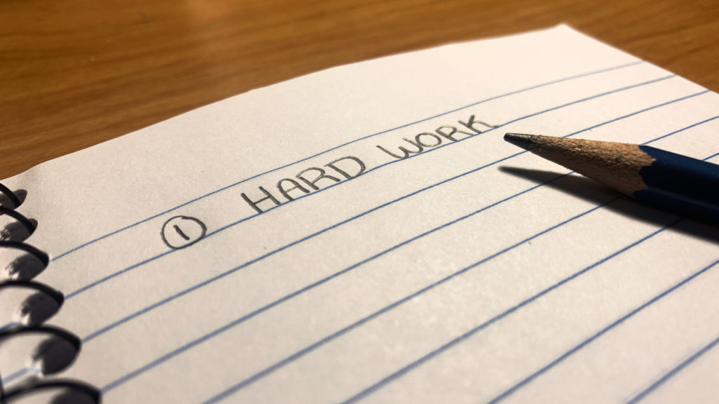 "In this image: A notebook with ""Hard Work"" written on it."